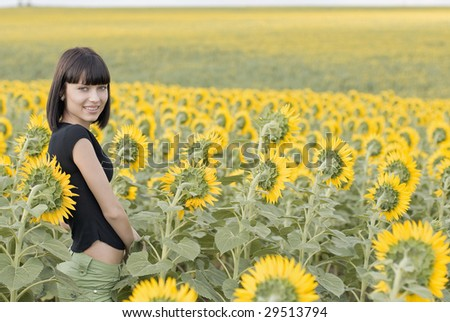 Young pretty woman on a sunflowers background - stock photo