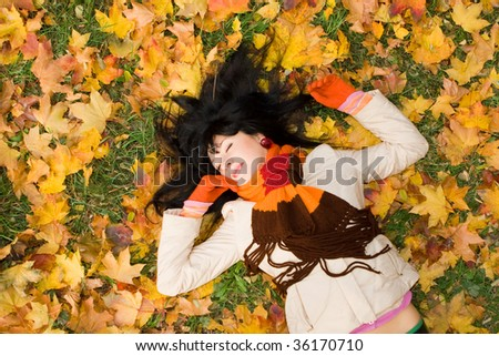Young pretty woman on the autumn leaf - stock photo