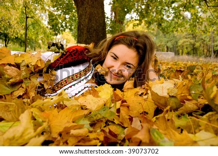 Young pretty woman on the autumn leaves