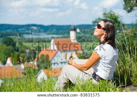 Young pretty woman on vacation. Looks at an old European city - stock photo