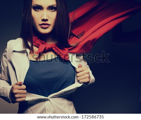 Young pretty woman opening her shirt like a superhero. Super girl, image toned. Beauty saves the world. - stock photo