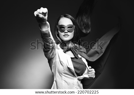 Young pretty woman opening her shirt like a superhero. Super girl, image toned. Beauty saves the world. Black and white. - stock photo