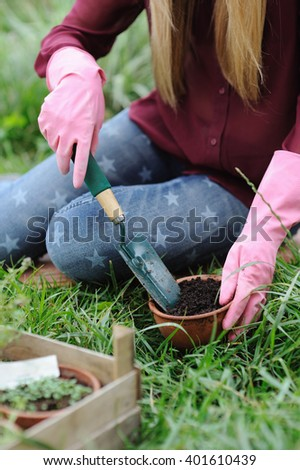 Young pretty woman planting young seedling in the garden
