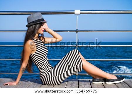 Young pretty woman posing at beautiful sea background.Wearing stylish stripe black and white dress and grey hat - stock photo
