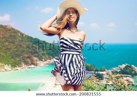 Young pretty woman posing at beautiful tropical island. Traveling in Koh Tao, Nang Yuan. Wearing stylish stripe black and white dress and retro hat. - stock photo