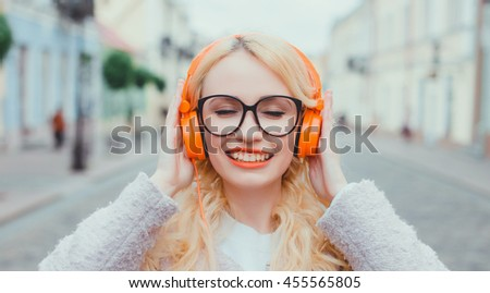young pretty woman posing in the street on headphones, listening music in earphones, hipster style, outdoor portrait, fashion model, chic, orange, colorful