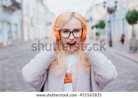 young pretty woman posing in the street on headphones, listening music in earphones, hipster style, outdoor portrait, fashion model, chic, orange, colorful - stock photo