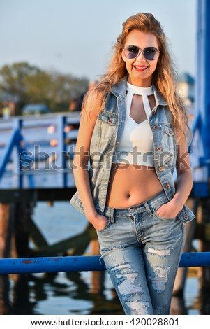 Young pretty woman posing on the pier wearing stylish denim suit.