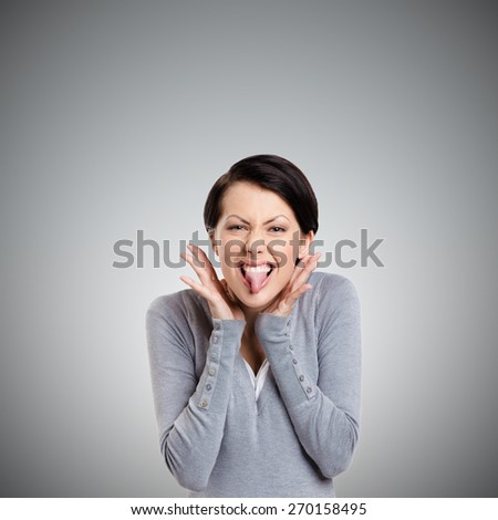Young pretty woman puts out tongue, isolated on grey - stock photo