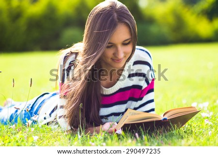 Young pretty woman reading book in city park at summer day