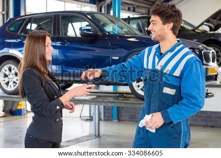Young, pretty woman, receiving the keys of her new used second hand car from a service mechanic at a car dealer garage - stock photo