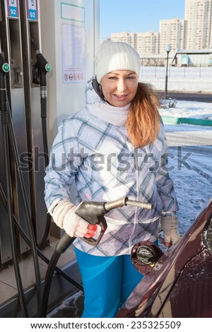 Young pretty woman refueling car with petroleum at winter season - stock photo