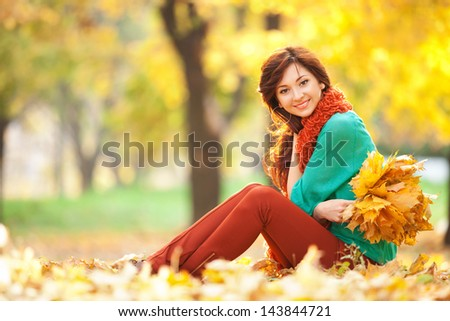 Young pretty woman relaxing in the autumn park - stock photo