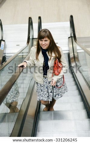 Young pretty woman rises on the escalator - stock photo