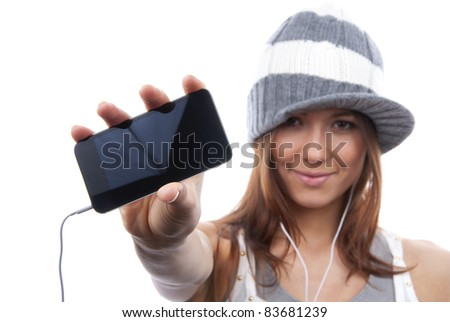 Young Pretty Woman Showing display of her new touch mobile cell phone and listen to music in earphonees. Focus on the hand and phone - stock photo