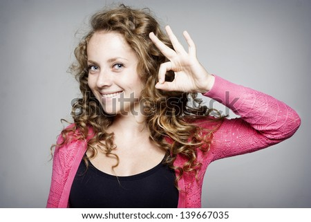 Young pretty woman showing hand ok sign - stock photo