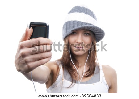 Young Pretty Woman Showing new touch mobile cell phone and listen to music in earphonees. Focus on the hand and phone - stock photo