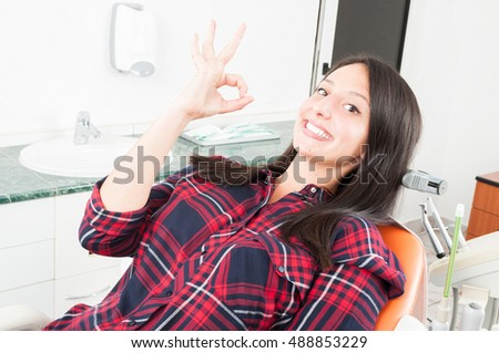 Young pretty woman showing okay gesture on dentist chair and smiling