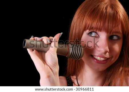 Young pretty woman singing with microphone on black background - stock photo