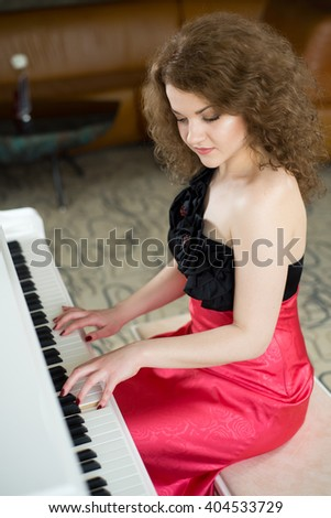 Young pretty woman sitting at the piano - stock photo