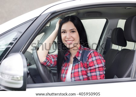 Young pretty woman sitting in the car, leaning on steering wheel, smiling and looking at camera - stock photo