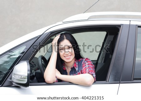 Young pretty woman sitting in the car, leaning on window, smiling and looking at camera - stock photo