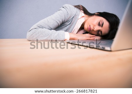 Young pretty woman sleeping on the table with laptop - stock photo