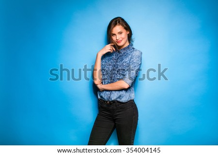 young pretty woman smilig in blue shirt standing confident blue background - stock photo