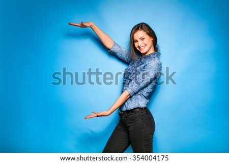 young pretty woman smilig in blue shirt standing with open hands on blue background - stock photo