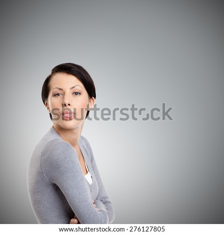 Young pretty woman sticks out tongue, isolated on grey - stock photo