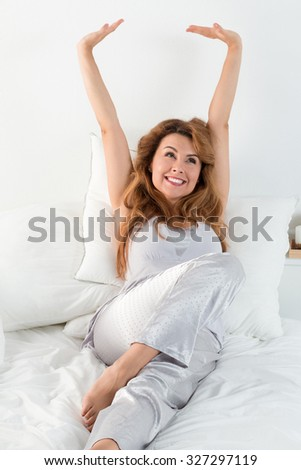 Young pretty woman stretches herself laying in her bed in the morning. Easy waking up and happy morning - stock photo