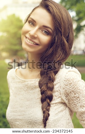 Young pretty woman summer outdoor portrait. Beautiful girl with stylish braid - stock photo