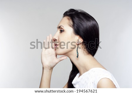 Young pretty woman telling gossip - stock photo