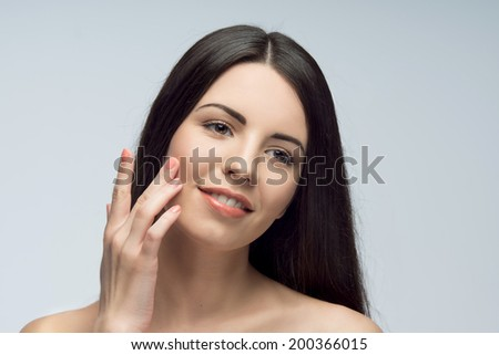 Young pretty woman, thinking about her clean and pure skin, isolated on the white background - stock photo