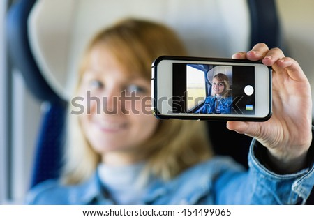 Young pretty woman traveling by train or bus, sitting near the window and taking selfie - enjoying travel.