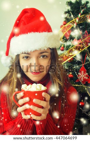 Young pretty woman under new year tree with christmas cup of chocolate