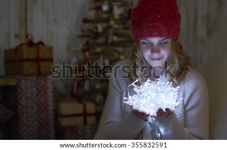 Young pretty woman under new year tree with christmas lights