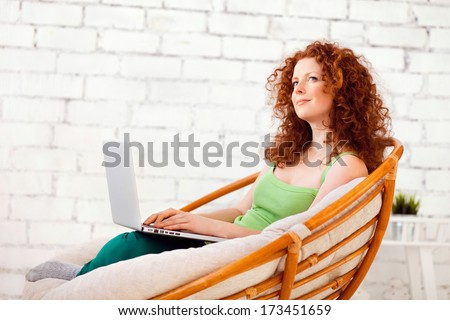Young pretty woman using a laptop computer at home - stock photo