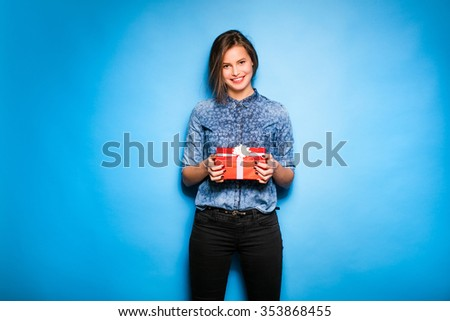 young pretty woman with a red gift in hands, standing and smiling on blue background - stock photo