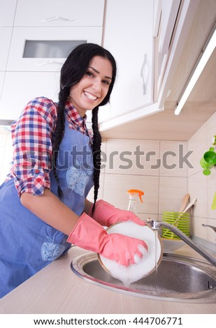 Young pretty woman with apron and protective gloves washing dishes in the kitchen - stock photo