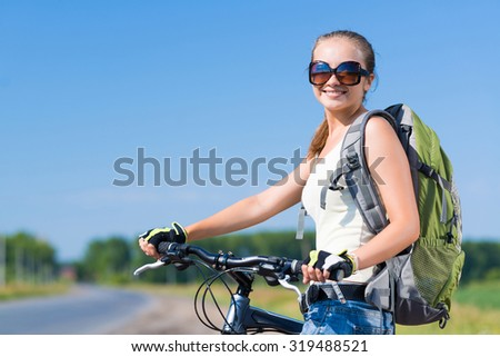 Young pretty woman with backpack riding bicycle outdoors - stock photo