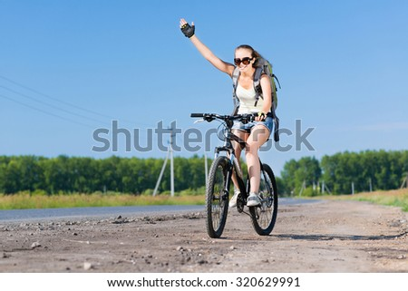 Young pretty woman with backpack riding bicycle outdoors and giving hand signal - stock photo