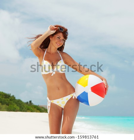 Young pretty woman with ball on the beach background - stock photo