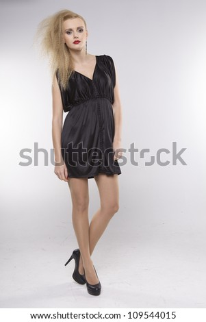 Young pretty woman with beautiful blond hairs and multicolor makeup in black dress isolated on white background