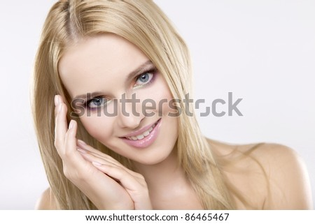 Young pretty woman with beautiful blond hairs and multicolor makeup isolated on white background