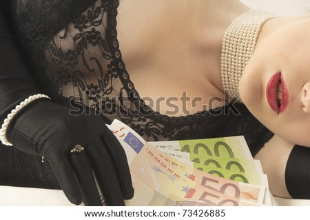 Young pretty woman with blonde hair holding a bundle of banknotes seductive in her hand, against a white background.