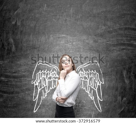 young pretty woman with hand to the chin and eyes up standing in front of a blackboard with angel wings painted on it as if they were hers. Concept of lending wings. - stock photo