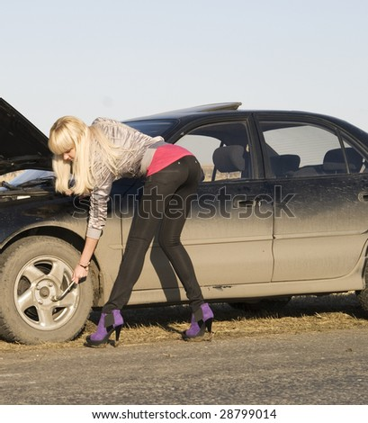 young pretty woman with her broken car