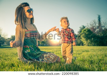 Young pretty woman with her son.Mom holding hand of a 1 year old boy - stock photo