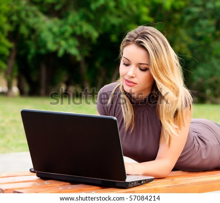 Young pretty woman with laptop lying on the bench in a park - stock photo